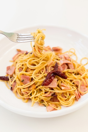 Spicy bacon spaghetti on white dish photo