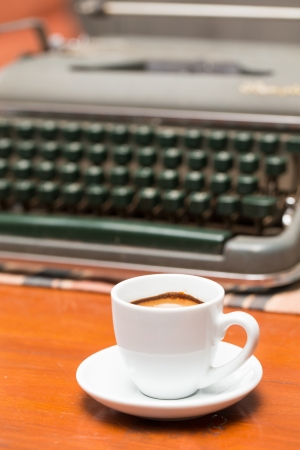 coffee cup and old typewriter on wooden table photo