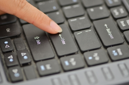 finger pressing the button of keyboard