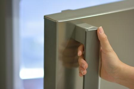 refrigerator with food: one hand opening refrigerator