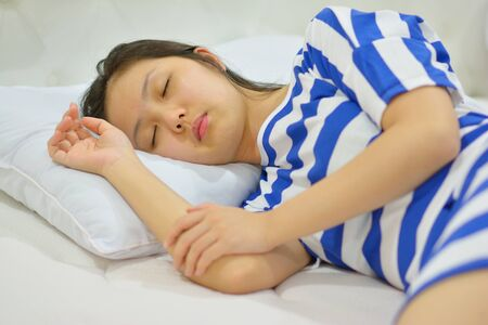 young woman sleeping on bed in bedroom