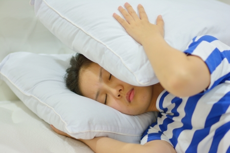 young woman suffering from insomnia and covering her head with a pillow