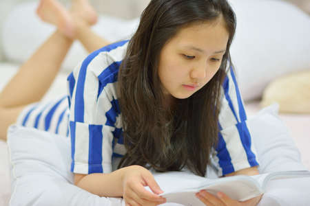 young woman reading a book in her bed