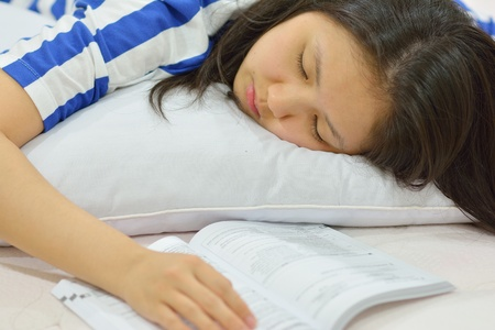 Teenage girl fall asleep while studying in bed
