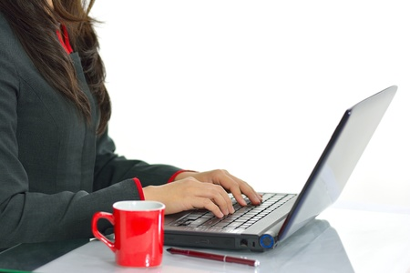 Female hands typing on laptop keyboard at office desk isolated on white background