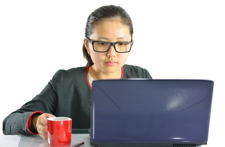 Young female concentrating on laptop computer screen, sitting at desk in office, holding mug on white background