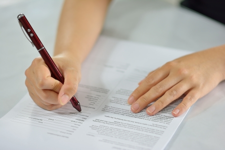 conclude: sitting at office desk signing the contract to conclude a deal Stock Photo
