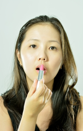 young asian woman using lipstick photo