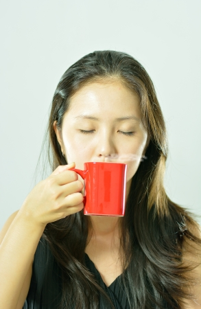 woman taking in smell of coffee with her eyes closed photo