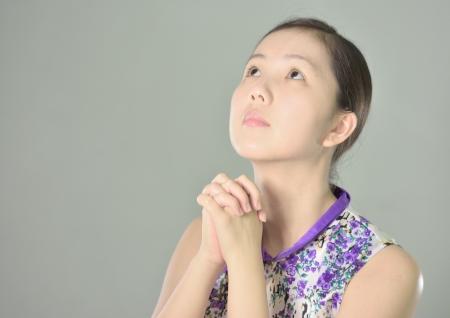 meditation pray religion: Closeup portrait of a young asian woman praying Stock Photo