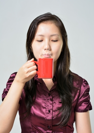 Beautiful woman drinking coffee, asian enjoy cup of hot chocolate,  portrait of female with morning tea, gorgeous woman holding cappuccino mug