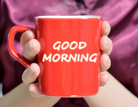 hands holding red mug of hot drink, close-up photo