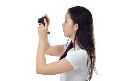 woman taking a photo with a camera on a white background Standard-Bild