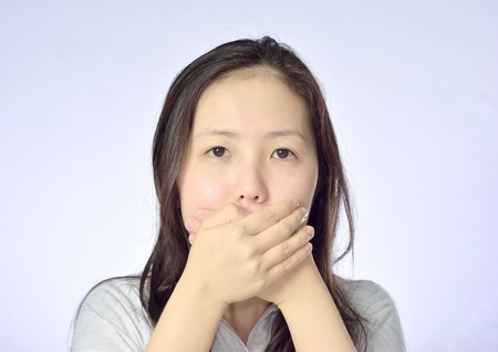Young asian woman covering her mouth photo