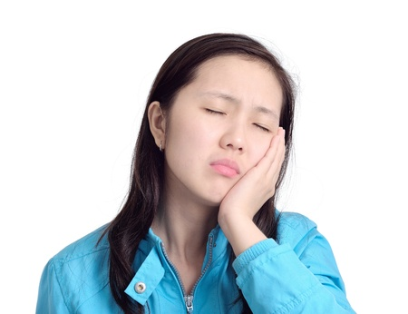 woman pressing her  cheek with a painful expression as if she s having a terrible tooth ache photo