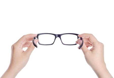 女性は白い背景に黒の持株眼鏡を手します。 写真素材
