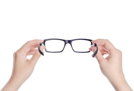 looking through an object: woman hands holding black eyeglasses on white background