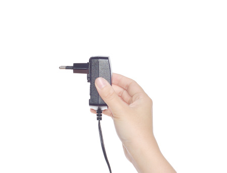 female hand holding cell phone charger  isolated on white Standard-Bild