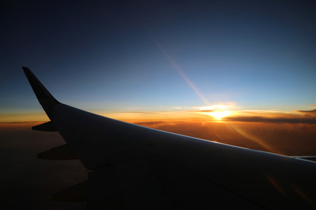 View on the sunrise and airplane wing from the inside
