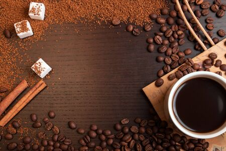 Cup of coffee, coffee beans, ground coffee sugar and cinnamon on dark brown table with