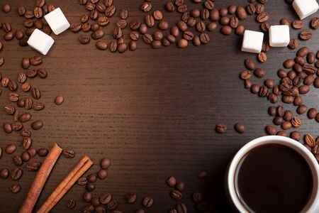 suger: Cup of coffee, coffee beans, sugar cubes and cinnamon on dark brown table with space for text