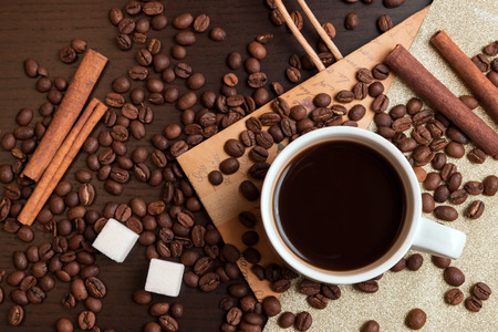 Cup of coffee, coffee beans, sugar cubes and cinnamon on dark brown table