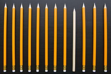 Rangée de crayons identiques avec un différent sur backgorund sombre
