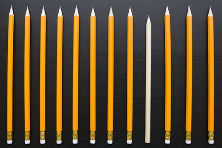 Row of identical pencils with one different on dark backgorund