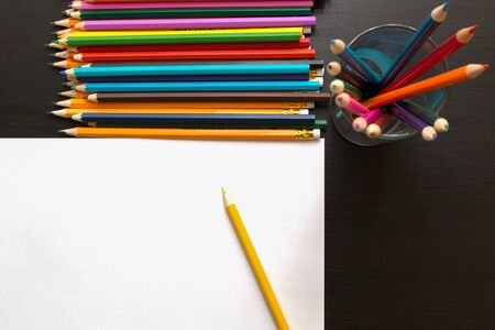 Colored pencils and sheet of paper on dark background Stock Photo