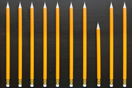 identical: Row of identical pencils with one different on dark background