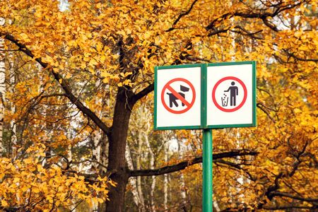 Prohibiting dog sign and prohibiting littering sign in forest. Nature pollution concept