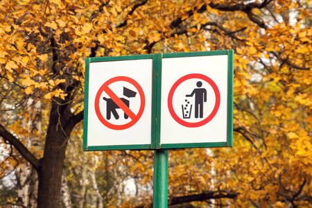 Prohibiting dog sign and prohibiting littering sign in forest. Environmental pollution concept