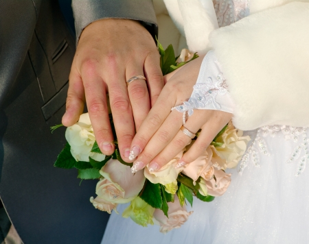 attaining: hand of groom and fiancee on a background a bouquet from roses