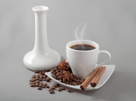 black coffee in a white mug stands on a saucer with the spilled grains on a background a white vase photo