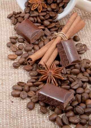 bob of coffee, chocolate, sticks of cinnamon, anise spilled from a cup on a background rough material photo