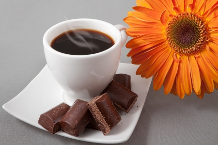 black coffee and chocolate on a background orange gerbera photo