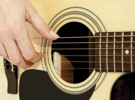 woman hand plucking strings on a guitar Stock Photo - 13751170