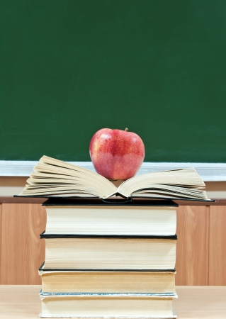 red apple lies on a pile from textbooks on a background a green school board photo