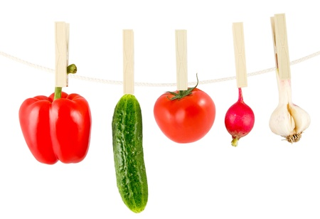 pepper, cucumber, tomato, garden radish, garlic to drying on a clothesline a clothes peg on a white background photo