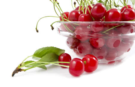 a cherry with a branch lies near a dish with a cherry Stock Photo - 13784299