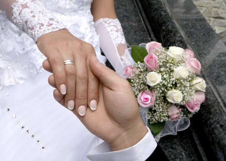 a man holds the hand of woman on a background a bouquet photo