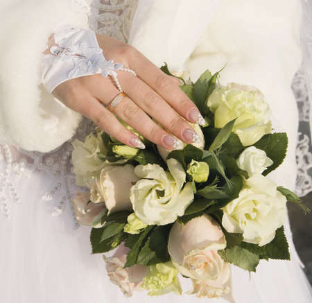 attaining:  hand of fiancee with a wedding ring lies on a bouquet from roses Stock Photo
