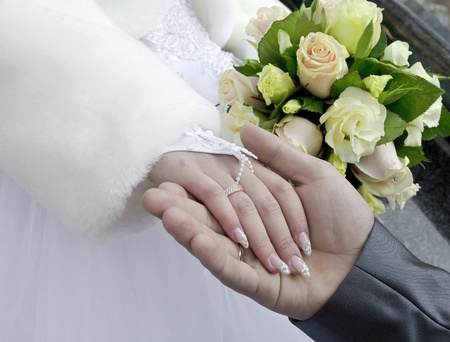 a woman hand with a wedding ring lies in a masculine palm on a background a bouquet photo