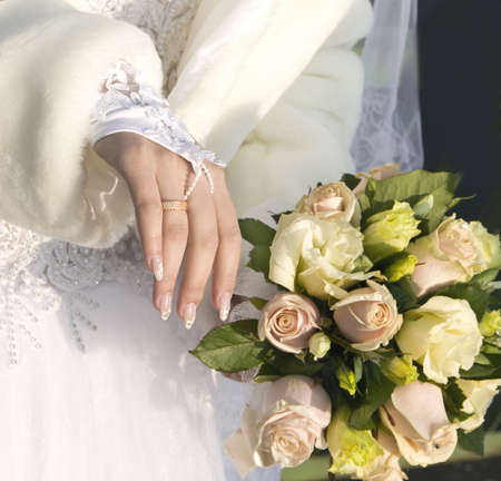 attaining: hand of fiancee with a wedding ring  a bouquet from roses