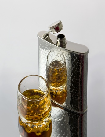 wineglass is gap-filling to whisky reflected in a steel flask Stock Photo - 13823461