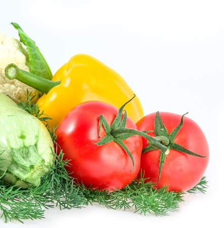 two tomatoes, pepper and vegetable marrow on white photo