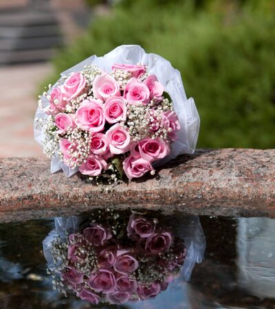 bouquet of the bride and pink roses lies on the edge of the fountain with the reflection in the water photo