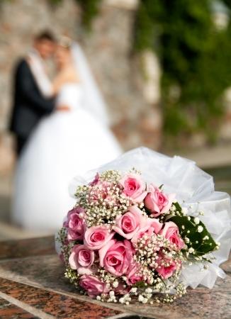 結婚式: バラの花束は、花婿と花嫁の背景にあります。