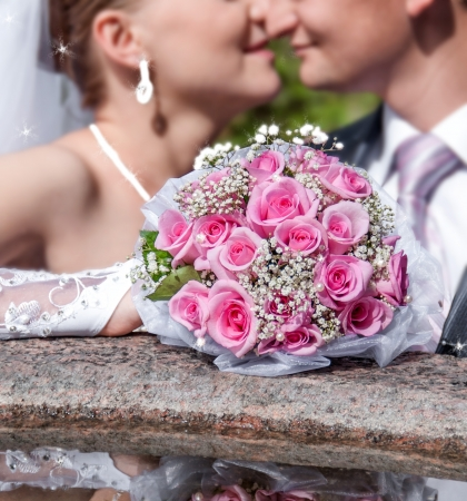 bride and groom kiss on the background of a bouquet of flowers