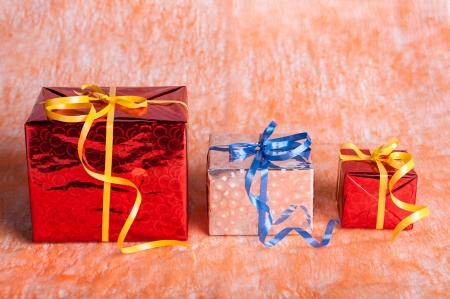 three gift boxes: tres cajas de regalo en un fondo anaranjado Foto de archivo